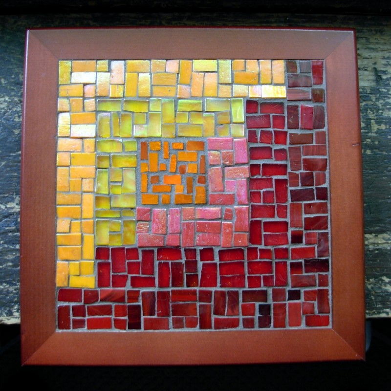 Asymmetric Log Cabin Trivet in Orange and Red by Margaret Almon. Glass on wood, 8 inches.