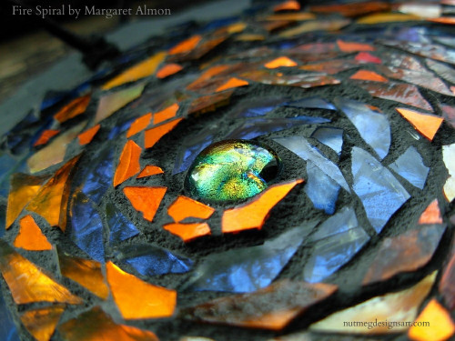 Fire Spiral Mandala by Margaret Almon. Glass, gold smalti, dichroic on slate, 7 inches.